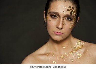 Gorgeous brunette female portrait with gold flakes on her face and hair in a bun on a black background.