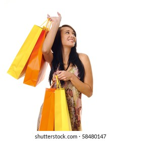 Gorgeous brunette girl with bright yellow and orange shopping bags
