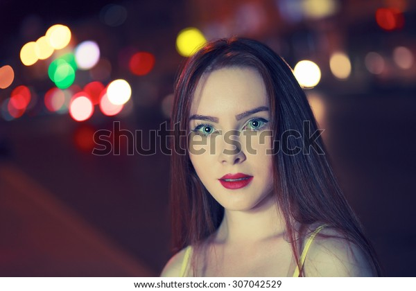 Gorgeous brunette girl portrait over night city defocused lights. Vogue fashion style portrait of young beautiful woman with long dark hair. Shallow DOF. Toned image with copyspace