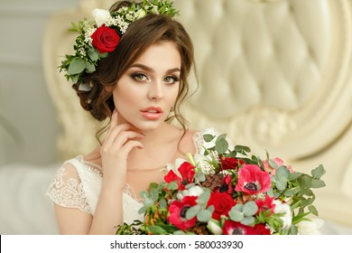 Gorgeous brunette girl smiling in a white dress, with a wreath and a bouquet, close-up