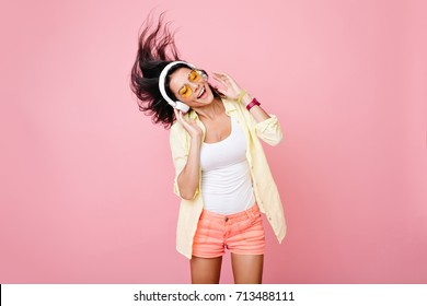 Gorgeous brunette lady in yellow glasses listening music in headphones and singing on pink background. Charming girl in shorts and earphones dancing with hair waving and eyes closed. - Shutterstock ID 713488111