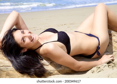 Gorgeous brunette laying on the beach with bikini