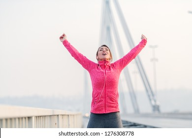 Gorgeous brunette lifting arms in the air and feeling free after running on the bridge. Winter time, healthy lifestyle concept.