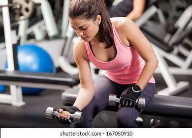 Gorgeous brunette lifting some weights and working on her biceps in a gym