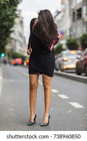 Gorgeous brunette with long hair covering her face.  Woman standing in the street wearing a chic black jersey dress and black leather pumps flipping her hair back.  Girl standing on street.