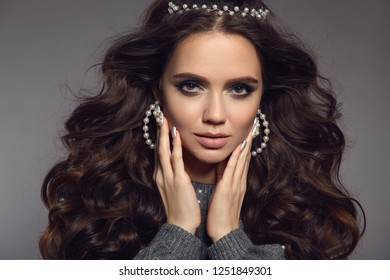 Gorgeous brunette portrait. Beauty makeup. Pearls jewelry set. Curly long hair style. Manicured nails. Sensual girl model with matte lipstick isolated on studio gray background.