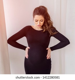 Gorgeous brunette pregnant woman at home in black dress