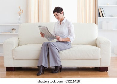 Gorgeous brunette reading the news in the living room