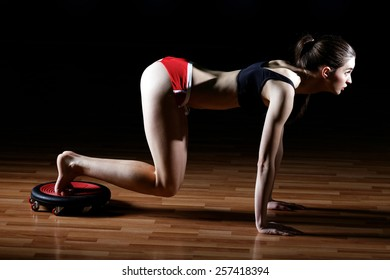 Gorgeous brunette warming up and doing some push ups a the gym. Attractive fitness woman, trained female body, lifestyle portrait, caucasian model.