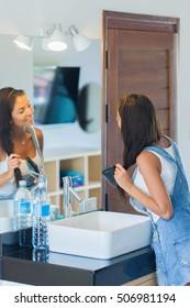 Gorgeous brunette woman brushing her hair in bathroom