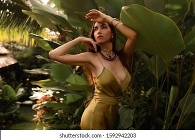 Gorgeous brunette woman in elegant silk dress posing in tropical garden.  Golden jewelry, bohemian style. Perfect face, bronze skin, dark hairs.