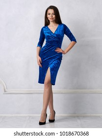 Gorgeous brunette woman with long hair dressed in elegant blue velvet midi dress with split front smiling and posing against white wall on background. Beautiful female model standing crossed legs.