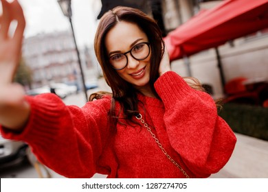 Gorgeous brunette woman with perfect smile  making self portrait by camera. Wearing red knitted sweater. Spring fashion.  Traveling girl walking around the city.