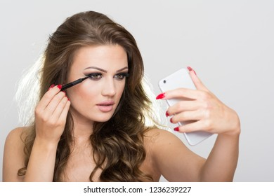 Gorgeous brunette young woman applying mascara looking at smartphone mirror