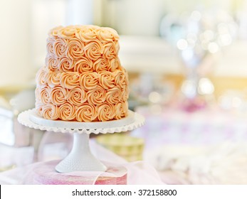 Gorgeous cake covered in roses made of butter cream icing sitting on a cake pedestal with a bokeh background
