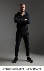 gorgeous casual man wearing tracksuit standing with crossed hands and strong posture on gray studio background