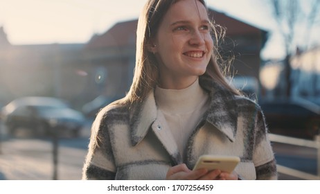 Gorgeous caucasian blondehair girl walking down the street, smiling, using phone, chatting with friends, looking around. Rays of the sun. Positive emotion.