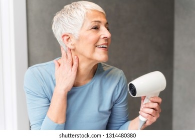 Gorgeous charming mature woman full of energy styling and drying her short gray hair with blowdryer at home