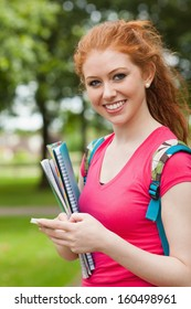 Gorgeous cheerful student holding notebooks texting on campus at college