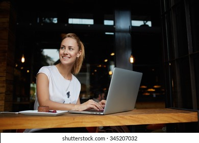 Gorgeous cheerful woman freelancer with good mood using laptop computer for distance work during lunch in cafe bar, attractive female with beautiful smile sitting with portable net-book in coffee shop