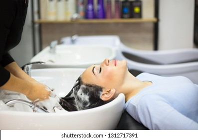 Gorgeous cheerful young woman enjoying head massage while getting her hair washed by a professional hairdresser.  Beauty care, hairstyling, fashion, lifestyle glamour concept