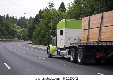 Gorgeous classic white and green big rig semi truck with chrome details with flat bad trailer transport wood lumber secured with slings for safe transportation running on windy road with green trees