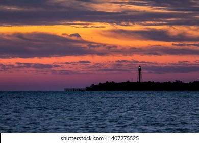 Gorgeous colors fill the sky at daybreak silhouetting the Point Ybel Light, a metal lighthouse on Sanibel Island, Florida.