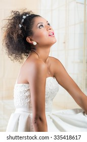 Gorgeous curly African American bride wearing white dress looking up