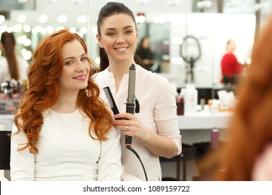 Gorgeous curly haired young woman and her hairdresser smiling looking in the mirror checking out stunning hairstyle copy space. Haircut, hair care, beautician concept