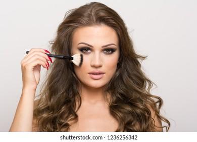 Gorgeous dark blonde hair young woman applying makeup on cheek using brush. No retouch, studio lighting, closeup.