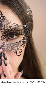 Gorgeous  dark haired woman with black makeup wearing a black carnival mask,bright black lipstick and nail polish,vintage theater style
