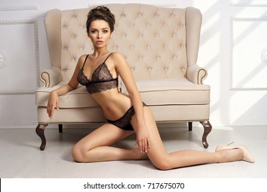 Gorgeous dark haired woman with elegant hairstyle dressed in black lingerie set and nude high heeled shoes sitting on white floor in sexy posture and leaning on light sofa standing behind her.