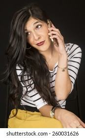 Gorgeous dark model sitting sering a striped top and a beautiful yellow skirt talking cell phone