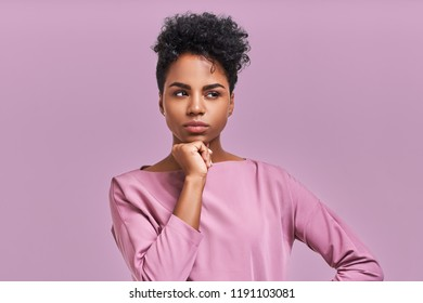 Gorgeous dark skinned young female with Afro hairstyle and confident look, poses for fashionable magazine, looks aside thoughtfully poses against lavender studio background.
