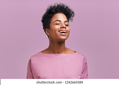 Gorgeous dark skinned young female winking at camera, keeping mouth wide opened standing against lavender studio wall background.
