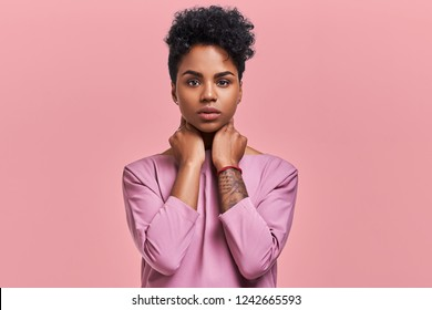 Gorgeous dark skinned young female with Afro hairstyle and confident look, poses for fashionable magazine, looks confidently at the camera, wears trendy shades, poses against a pink studio background.