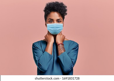 Gorgeous dark skinned young female with Afro hairstyle wearing protective mask against COVID virus, tired of stress and tension, looks confidently at the camera, poses against beige studio background