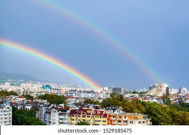 Gorgeous double rainbow over city. A double rainbow appeared against gray stormy sky over residential area of the city. Beauty in nature.