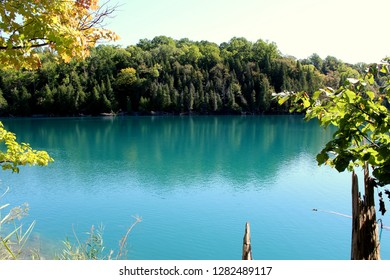 Gorgeous, dreamy image of blue-green lake made when glaciers melted but frigid water did not mix with the warmer water below, surrounded by trees, shrubs and sky.