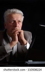 Gorgeous elderly man in suit on black background