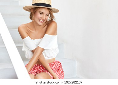 Gorgeous elegant restful smiling female model in hat, stylish clothing, looks with happy expression down, feels embarrassment as recieves compliment from boyfriend. Beauty and positiveness concept