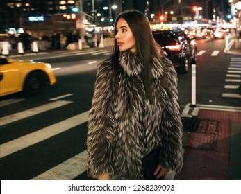 Gorgeous elegant woman walking on night city street wearing fake fur jacket and holding bag looking to the side
