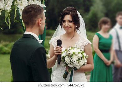 Gorgeous emotional bride in stylish white wedding dress with bouquet taking vow during outdoor wedding ceremony near aisle to handsome groom, her eyes tearing up