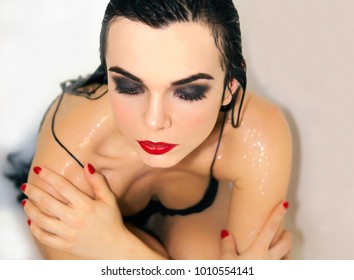 Gorgeous erotica artist. Beautiful woman portrait in a milk bath. Red lipstick on a lips and black lingerie. Perfect adorable make up.