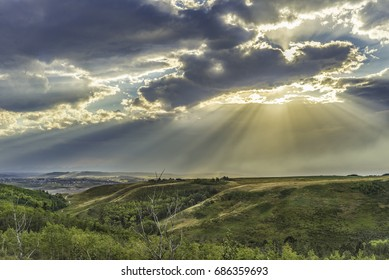 Gorgeous evening sky of Southwestern Alberta at Glenbow Ranch Park in the foothills west of Calgary. Sun beams bathe the distant Rocky Mountains and rolling green valley.