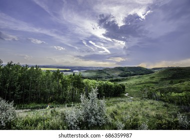 Gorgeous evening sky of Southwestern Alberta at Glenbow Ranch Park in the foothills of Alberta. Clouds form a majestic pattern over the grasslands and rolling hills leading to the Rocky Mountains.