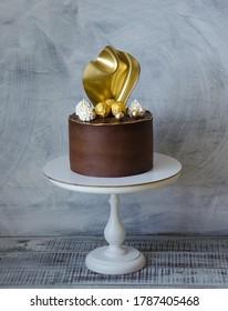 Gorgeous extra chocolate cake with gilded glaze and twist