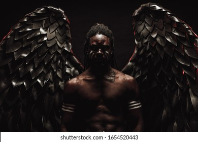 gorgeous and fantastic dark angel having big black wings, african male with strong body stand in the flesh of angel, white strips on muscular hands and dreadlocks on head. isolated photoshot