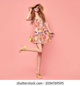 Gorgeous Fashion Lady Smiling in Floral Dress. Trendy wavy Hairstyle. Sexy Young Model, Stylish Sunglasses, fashionable Hat. Playful Summer Girl in Yellow Heels