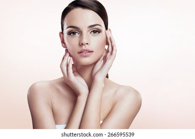 Gorgeous fashion model on beige background. Youth and skin care concept.